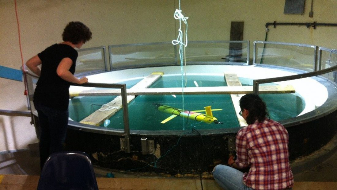Graduate students Gennavieve Ruckdeschel and Tara Howatt submerge the glider into a 30 m deep seawater tank at Dalhousie to prepare the echosounder sensor for measuring zooplankton at sea.