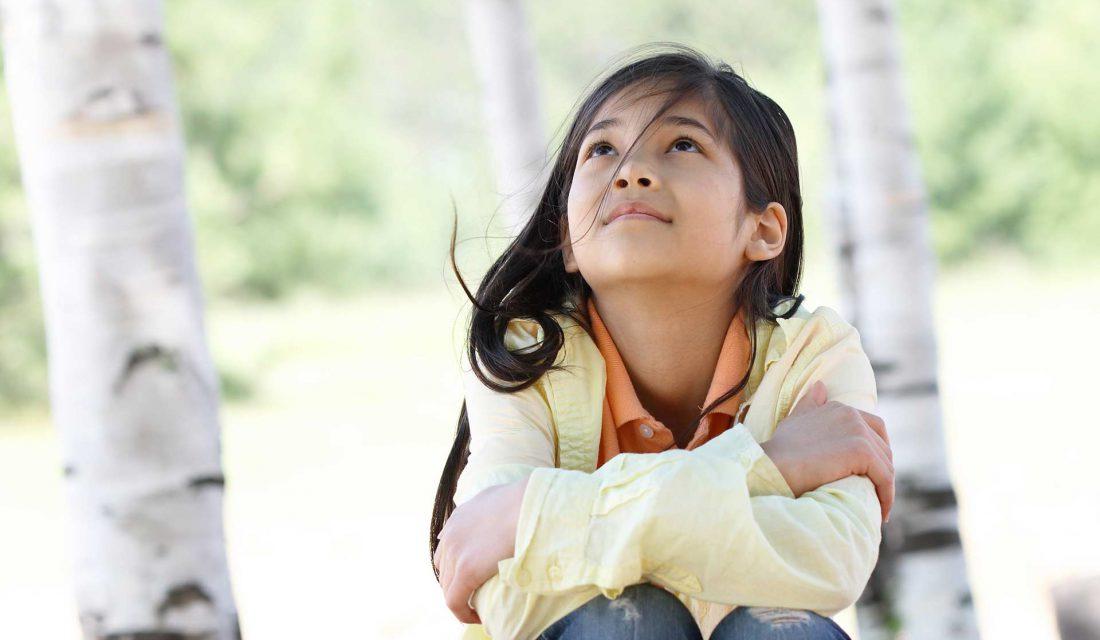 girl outside sitting under trees