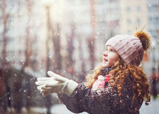 girl in the snow in an urban area